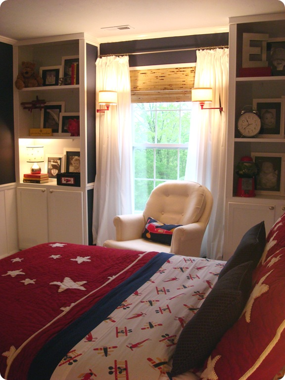 Bookcases around window with sconces