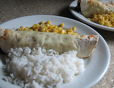 A shredded beef and Chile enchilada on a white plate with corn and white rice on the side.