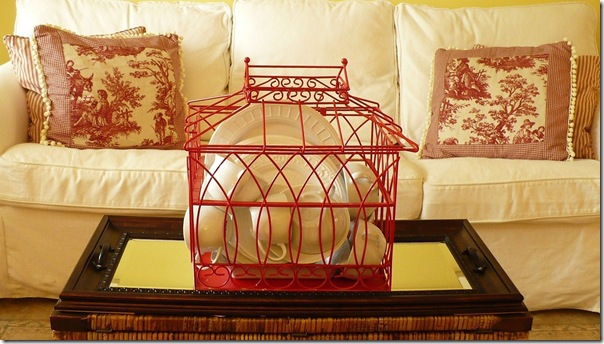 red bird house filled with white dishes