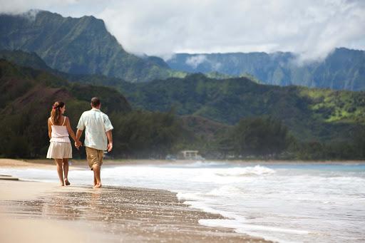 A couple walks along the beach in Kauai.