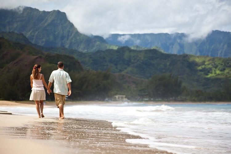 A couple walks along the beach in Kauai.