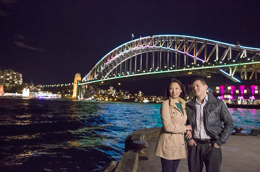 Vivid_Sydney_Festival - A couple takes in the Vivid Sydney Festival along Walsh Bay with the Sydney Harbour Bridge as a backdrop.