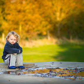 frowning child by Keren Woodgyer - Babies & Children Children Candids ( child, sitting, autumn, outdoors, frowning, puddle, alone, sun, golden, outside )