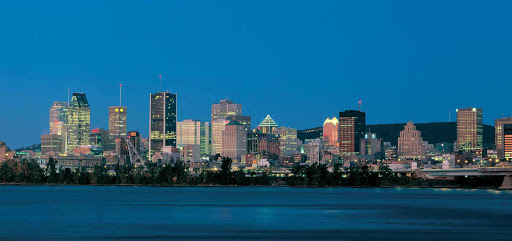 The Montreal skyline over the St. Lawrence River at nightfall.