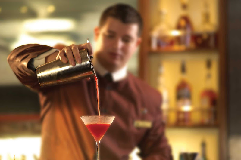 A crew member prepares a cocktail at the Commodore Club on Queen Mary 2.