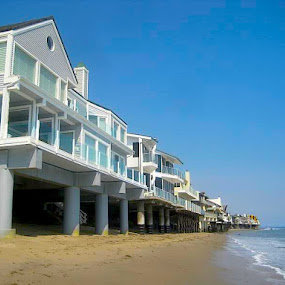 Living on the Beach in Malibu, CA by Ronnie Caplan - Buildings & Architecture Homes ( water, sand, vertical lines, waves, white, pacific ocean, windows, beach, pilings, coastline, structures, pwc, sky, blue, malibu, buildings, pier, homes, , Beach, sunset, ocean.  )