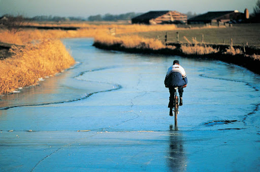 bicycle-winter-landscape-Holland - A cyclist on a frozen canal in the Netherlands.