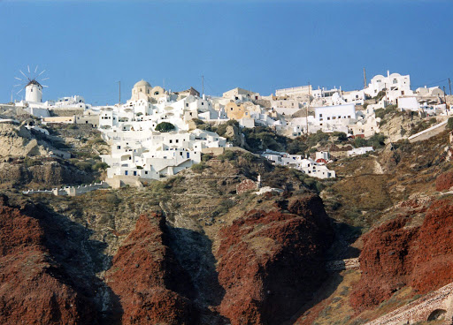 Oia-Santorini-hilltop - The sugar cube houses of Oia perch atop red rock cliffs that loom over the Aegean Sea on the magical island of Santorini.