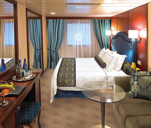 The D Level Ocean View staterooms on Oceania Nautica contain a queen bed with 1,000-thread-count linens, sofa, vanity desk, breakfast table, refrigerated mini-bar, Bulgari amenities, flat-screen TV with live satellite and twice-daily maid service. At 165 square feet, they're on deck 3.