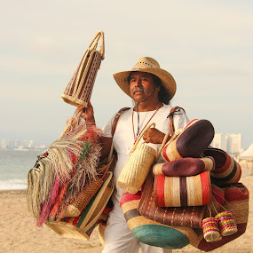 Vendor in Puerto Vallarta by Judith Dueck - People Portraits of Men ( shop, buy, straw, travel, beach, hats, sky, purses, smiling, clothes, colors, mexico, mexican, tourism, sales occupation, souvenirs, sale, holiday, salesman, vacation, market, dress, day, cheap, culture, hands holding, linen, cotton, gift, mexican   display, colorful, clothing, tropical, purchase, ocean, jewelery, business, sell, tradition, looking at camera, fabric, man, sand, ethnic, handbags, vendor, male, poor, sea, traditional, adult, spend, product, outdoor, summer, local, ethnicity )