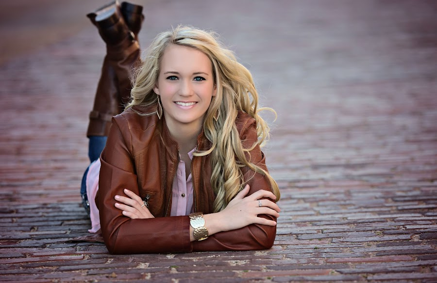 the smile by Carole Brown - People Portraits of Women ( leather jacket, blonde hair, blue eyes, laying on street., boots )