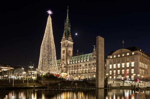 Germany-town-hall-at-christmas - Christmas illuminations light up the evening sky outside the town hall of Alster on the Elbe River in Northern Germany.