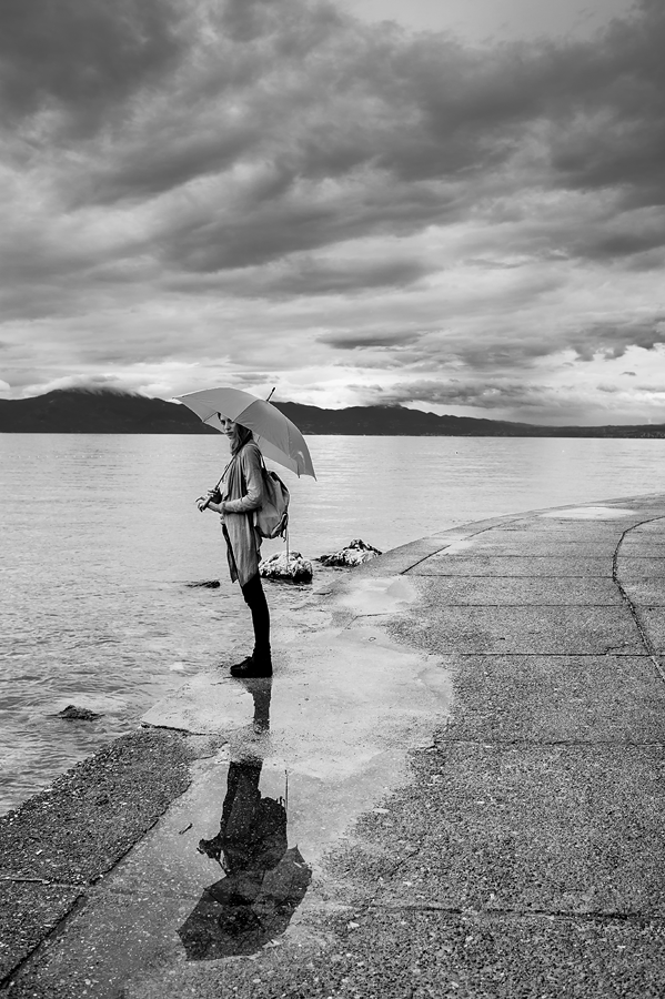 Water meets the sky by George Mihes - People Street & Candids ( clouds, mountains, sky, girl, umbrella, white, sea, puddle, black, sidewalk,  )