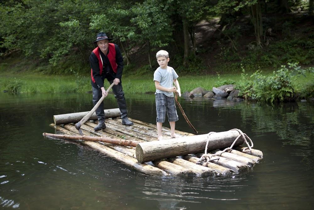Du siehst einen Mann und einen kleinen Jungen beim Floßfahren