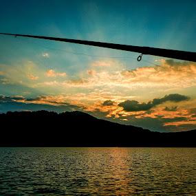 Fishing with joyfulness by Zec Mladen - Landscapes Sunsets & Sunrises ( hills, sunset, sunrays, lake, fishing )