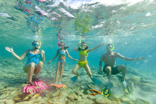 snorkeling-family-Aruba - A family enjoys snorkeling in the crystal clear waters of Aruba.