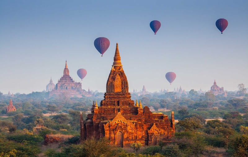 Hot air balloons hover above some 3,000 Buddhist temples during a sunrise flight in Bagan, Myanmar. You can now visit Bagan, Yangon, Mandalay and other breathtaking sites aboard AmaWaterways' luxury river cruise ship the AmaPura.