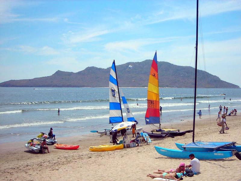 Sailboarders and catamarans on the beach in Mazatlan, Mexico.