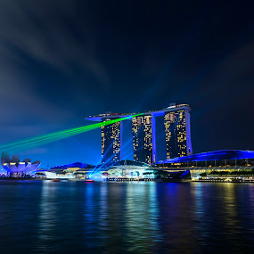 light shows a panorama of Singapore by Naďa Murmakova - Buildings & Architecture Office Buildings & Hotels ( skyline, harbor, travel, architecture, historic, attraction, city, sky, marina, light, central, structure, symbol, tourism, dusk, landmark, tourist, bay, scene, bridge, view, flyer, reflection, landscape, business, singapore, modern, skyscraper, southeast, asia, district, evening, downtown, water, office, building, beautiful, sea, aerial, vacations, hour, urban, tower, blue, sunset, night, hotel, celebration, esplanade, river,  )