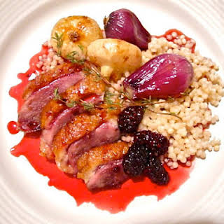 Crispy Duck with Blackberry Gastrique, Roasted Pearl Onions, and Israeli Cous-Cous.