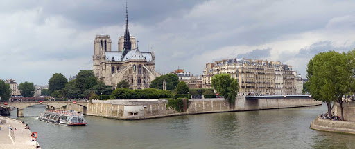 Notre-Dame-river-cruise-Paris - A river cruise ship sails past Notre Dame de Paris on Ile de la Cite in Paris.