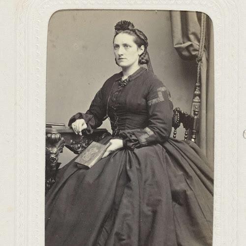f709bef43c34b9 Studioportret van een vrouw op een stoel in een lange zwarte jurk ...