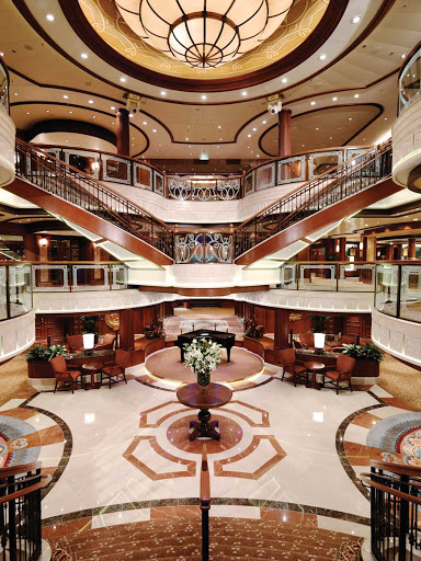 Cunard-Queen-Victoria-Grand-Lobby - Queen Victoria's stately Grand Lobby features a double sweeping staircase, sculpted balconies and a ceiling that extends three decks high.