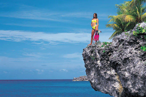 woman-snorkeler-overlook-Jamaica - A snorkeler surveys the lagoon from a rock outcropping in Jamaica.