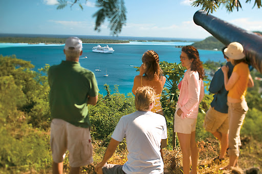 Guests of the Paul Gauguin on an outcropping look over Bora Bora's lagoon.